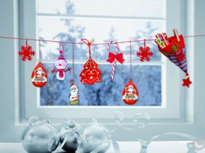 Fili stesi alla finestra: filo rosso, mollette, stelle e albero di panno, bastoncino di zucchero, pupazzetto di neve, berrettino, appendibili Kinder e barrette Kinder cioccolato