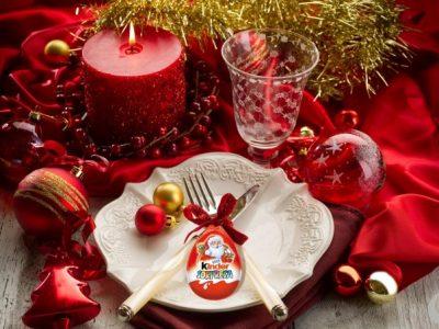Tavola in rosso(servizio di piatti da portata e bicchieri eleganti e decorati): palline varie con gancetti, posate manico madreperla, drappo rosso, candela rossa, festone oro e Kinder Sorpresa appendibile
