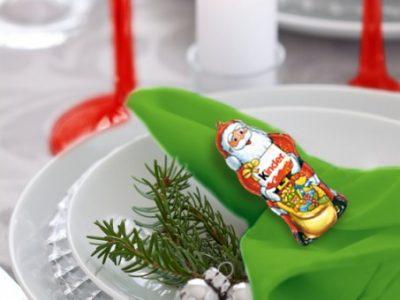 Tovagliolo verde, calice rosso, piatti bianchi e figura cava di Babbo Natale, rametto di abete e qualche grossa perla