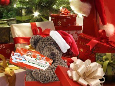 Un peluche a forma di orso, un berretto da Babbo Natale e una confezione di Kinder Cioccolato Auguri
